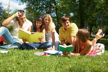 Portrait of cheerful friends talking and reading in park together photo