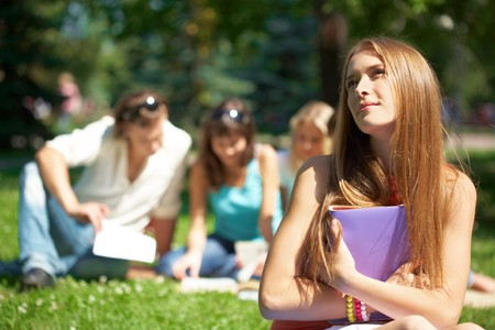 Portrait of teenage girl with book in hands on background of her reading friends photo