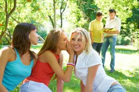 Photo of three girls whispering with each other about guys on background photo