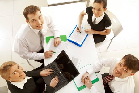 Several white collar workers looking upwards at camera from their workplaces Stock Photo - 7553049