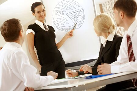 successful female standing by whiteboard while explaining her idea to colleagues Stock Photo - 7553048