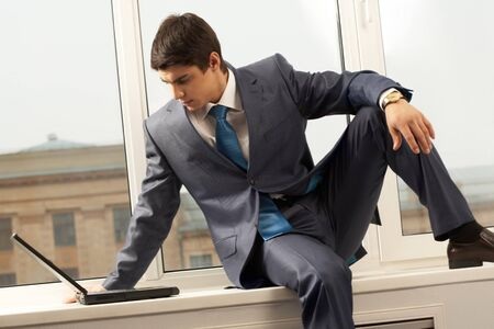 windowsill: smart businessman sitting on window-sill with laptop near by and looking at monitor