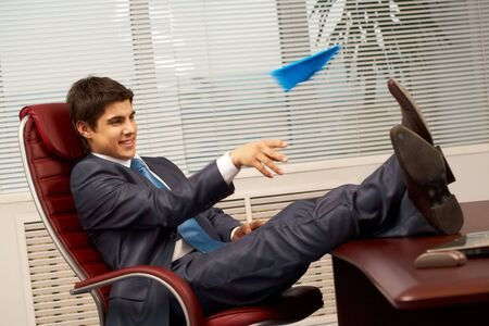 Smart businessman sitting in arm-chair in office and having fun during break photo
