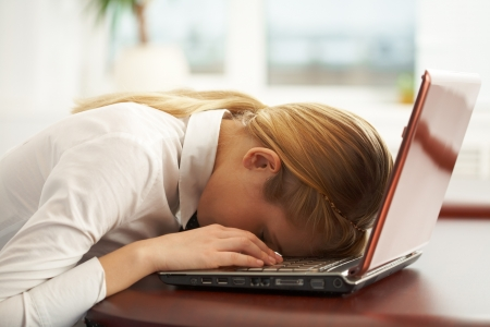 Image of very tired businesswoman or student with her face on keyboard of laptop photo