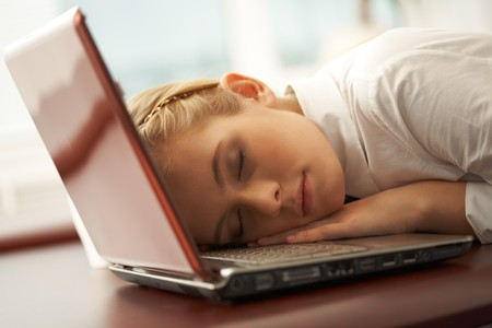 after work: young pretty girl having a nap just right on laptop keyboard after work Stock Photo
