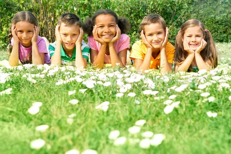 multiracial groups: Portrait of cute kids lying on green grass and looking at camera