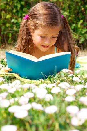 Portrait of cute schoolgirl reading interesting book in natural environment photo