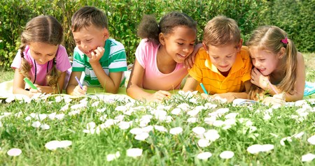 Portrait of cute kids drawing in natural environment together photo
