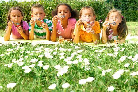 Portrait of cute friends having bubble fun on green lawn in park photo