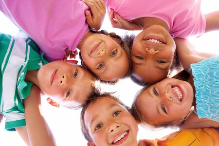 kid friendly: Below view of happy children embracing each other and smiling at camera