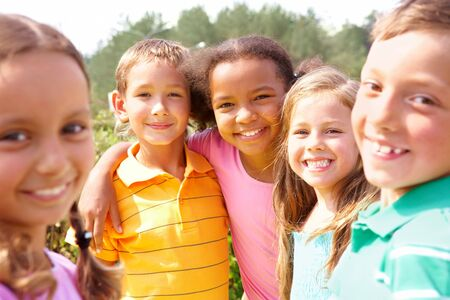 multiracial groups: Portrait of happy preschoolers looking at camera while embracing Stock Photo