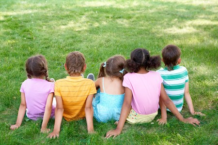 sit: Back view of cute kids seated on green grass and relaxing