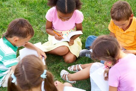 kids writing: Portrait of cute kids seated on green grass with copybooks and pencils Stock Photo