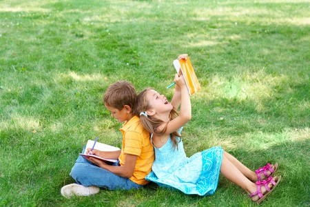 Portrait of cute kids seated on green grass with copybooks and pencils and drawing photo