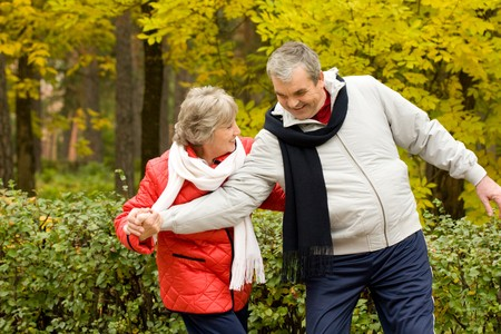 Photo of two aged people having fun during walk in autumn forest photo