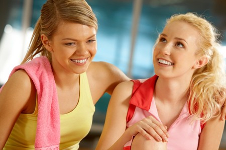 Portrait of two pretty girls during workout in gym photo