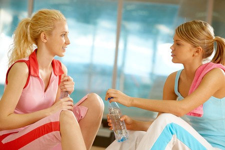 Photo of two teenage girls sitting in the sports gym and communicating photo