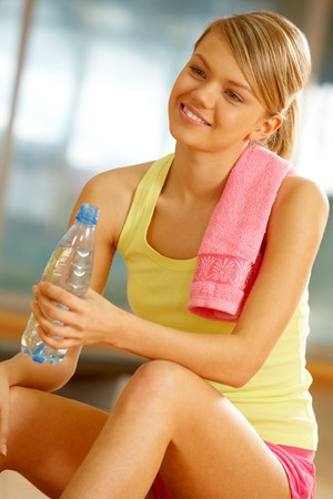 Portrait of happy woman wearing yellow tanktop looking aside with smile in gym Stock Photo - 7561222