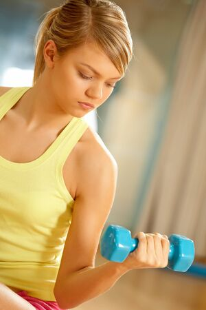Portrait of young female with dumbbells doing exercises for strong arms Stock Photo - 7561218