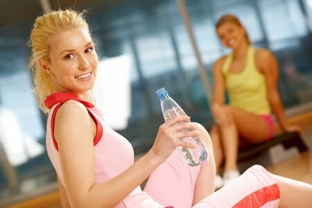 Happy girl sitting on mat with bottle of water with her friend on background Stock Photo - 7561198