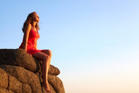 cliff edge: Photo of serene female seated on rock and relaxing Stock Photo