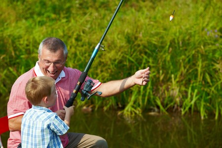 relatives: Photo of grandfather and grandson fishing in summer