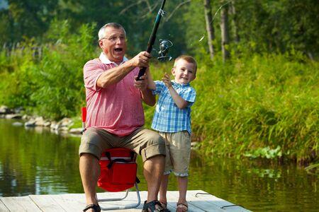 grandfather: Foto del abuelo y nieto, lanzando los aparejos de pesca en el entorno natural