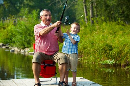 grandparent: Photo of grandfather and grandson throwing fishing tackle in natural environment
