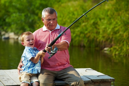 Photo of grandfather and grandson pulling rod while fishing on weekend photo