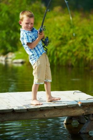 piedi nudi ragazzo: Foto del piccolo bambino tirando asta durante la pesca sul fine settimana  Archivio Fotografico