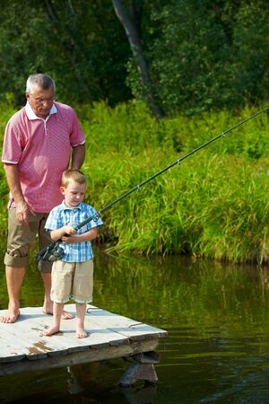 grandson: Photo of grandfather and grandson on pontoon fishing on weekend