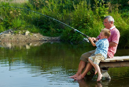 anglers: Photo of grandfather and grandson sitting on pontoon with their feet in water and fishing on weekend