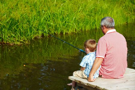 pontoon: Photo of grandfather and grandson sitting on pontoon and fishing on weekend Stock Photo