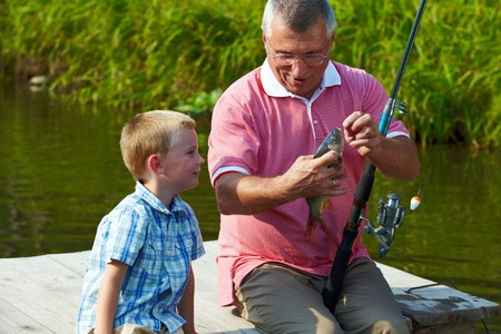 fishing lure: Photo of grandfather and grandson looking at fish caught by them Stock Photo
