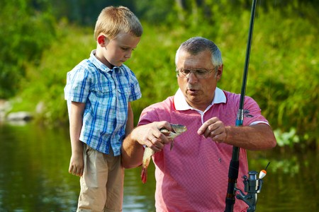 Photo of grandfather and grandson looking at fish caught by them photo