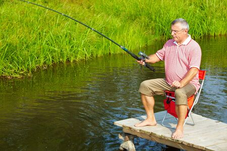 Photo of senior man fishing on weekend photo