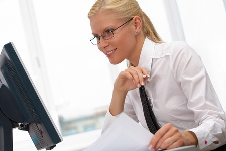 secretary woman: Image of young successful employer looking at computer monitor on workplace