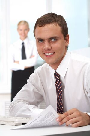 Portrait of confident boss holding papers at workplace with executive secretary standing behind Stock Photo - 7601897