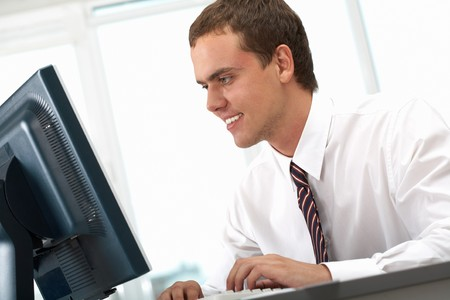 Image of young successful employer looking at computer monitor on workplace Stock Photo - 7601876