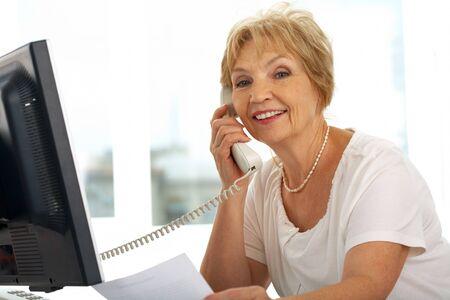 talkative: Portrait of senior female calling and smiling at camera Stock Photo