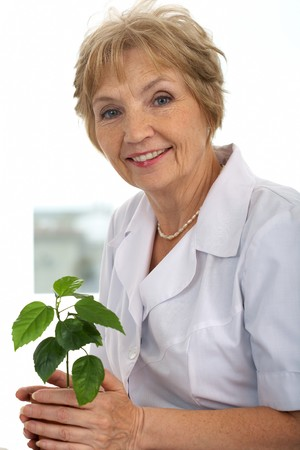 Portrait of kind and friendly woman with green plant Stock Photo - 7601931