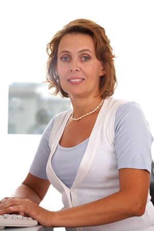 one mid adult woman: Portrait of middle-aged female typing and looking at camera