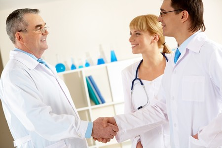 clinician: Photo of aged physician and young clinician looking at each other while handshaking with pretty nurse near by Stock Photo
