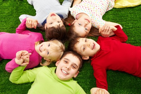 Image of smiling young boys and girls lying on green grass Stock Photo - 7602187