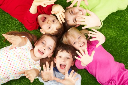 altogether: Image of smiling young boys and girls lying on green grass and showing palms Stock Photo
