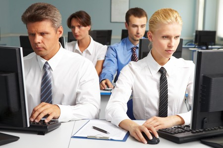 Businesspeople sitting at tables and looking at their monitors Stock Photo - 7602222