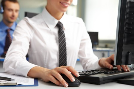 Image of female hand on mouse while typing on keyboard in a working environment   photo