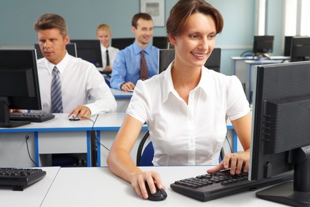 Businesspeople sitting at tables and looking at their monitors with smiling woman at foreground photo