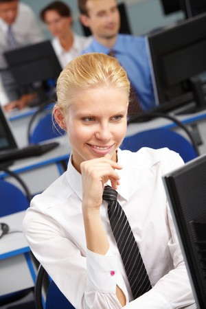 Businesswoman looking at monitor with smile in working environment photo