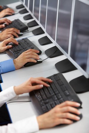 Image of row of human hands typing in computer classroom photo